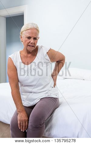 Senior woman suffering from back pain while sitting in bedroom at home