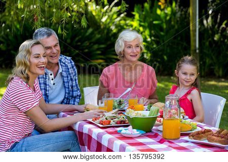 Happy family having meal at table in yard