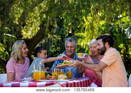 Happy family enjoying while having meal at table in yard