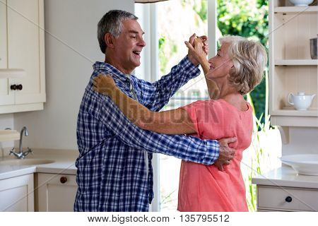 Happy senior couple dancing in kitchen at home