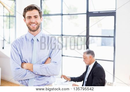 Smiling businessman crossing arms in front of working businessman in office