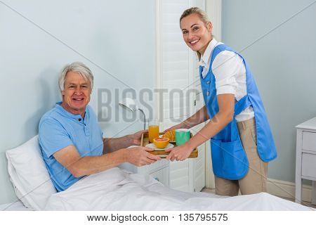 Portrait of nurse giving breakfast to smiling senior man at home