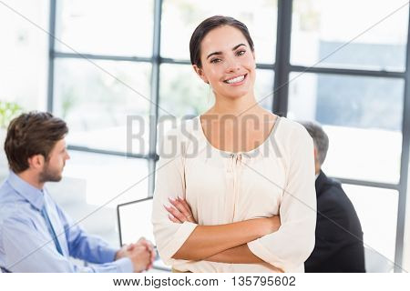 Pretty businesswoman smiling with arms crossed in office