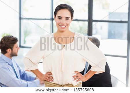 Pretty businesswoman smiling with hands on hips in office