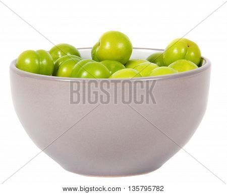 cherry-plums in bowl on the white surface