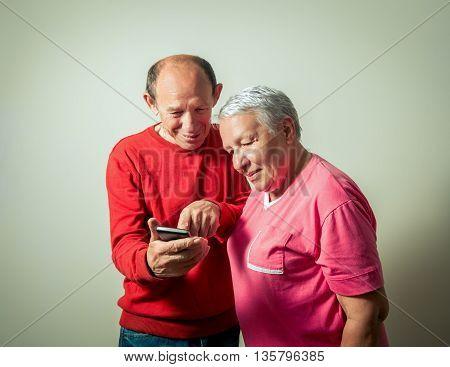portrait of the senior couple using phone