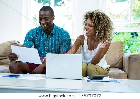 Happy couple checking bills while using laptop in living room