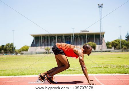 Determined athlete on a starting block about to run