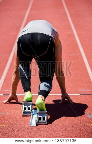 Rear view of determined athlete on a starting block about to run