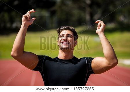 Happy athlete posing after victory on running track