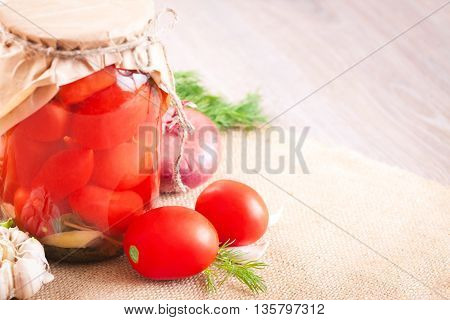 Canned tomatoes with garlic and herbs in a glass jar on the wooden table