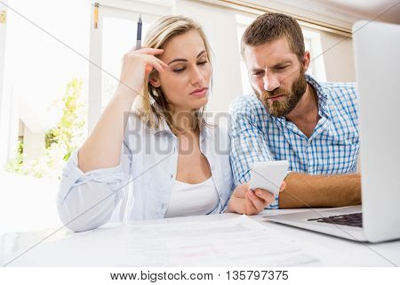 Couple looking at mobile phone at home