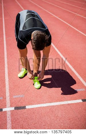 Male athlete tying his shoe laces on running track on a sunny day