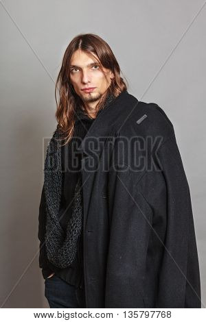 Portrait of handsome fashionable man wearing black sweater and scarf holding coat. Young guy posing in studio. Winter or autumn fashion.