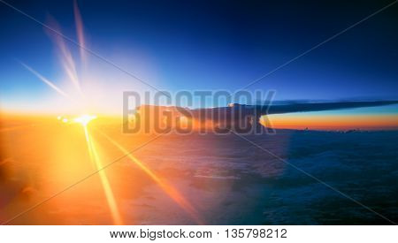 Beautiful Panorama Of Sunset Over Mountains From Height Of Airplane. Bright Blue, Orange, Yellow Colors Of Sunrise Sky. Warm And Cold Colors. Toned Filtered Instant Photography Image.