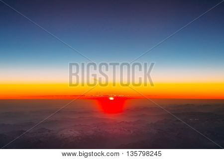 Amazing Beautiful Sunset Sunrise Over Horizon Mountains From Height Of Airplane, Plane. Bright Blue, Orange, Yellow And Blue Colors Of Sunrise Sky Background. Bright Colorful Sky Over Dark Ground