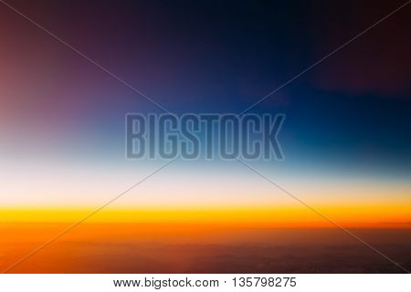 Beautiful Scenic View Of Sunset From Height Of Airplane. Dark Sunrise Sky. Warm And Cold Colors.