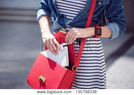 Everything in order. Close up of handbag of a woman opening it and putting book inside while having a walk
