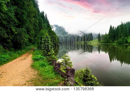 Misty sunrise with clouds on the Red Lake Romania
