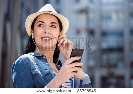 My hobby. Cheerful delighted smiling young woman holding cell phone and listening to music while having a walk