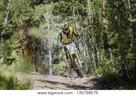 racer on a motorcycle rides along stone track in forest