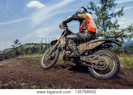 rider going down a hill dirt and stones from under wheels