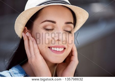 On the edge of delight. Portrait of cheerful young woman touching her ears and feeling content while listening to music