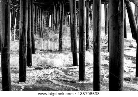 waves crashing in under a pier in black and white