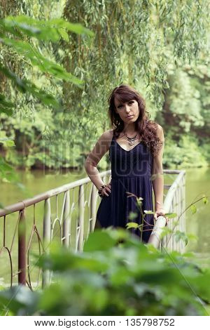 Beautiful woman in sundress on the pond bridge in the forest