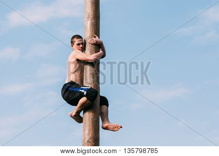 Gomel, Belarus - March 12, 2016: Young man climbs on a wooden post on the traditional holiday dedicated to the approach of spring - Slavic celebration Shrovetide.