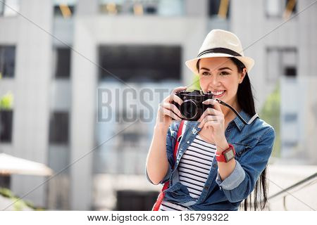 Catch the moment. Pleasant beautiful delighted smiling woman holding camera and having a walk while taking photos
