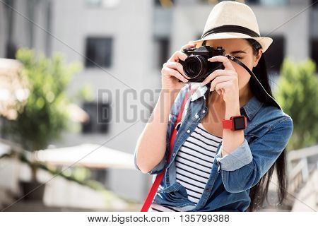 Involved in hobby. Pleasant delighted young woman holding photo camera and making shots while having a walk