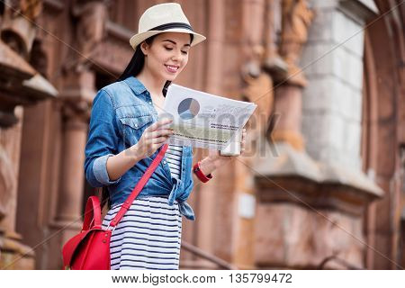 In whirlwind of life. Pleasant charming smiling young woman drinking coffee and reading newspaper while walking outside