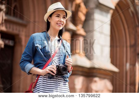 Open up the world. Pleasant delighted smiling young woman standing in the street and expressing gladness while having a walk
