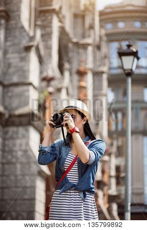 Like what you do. Pleasant young woman holding photo camera and making shots while having a walk