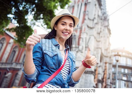 Full of emotions. Positive beautiful smiling woman standing in the street and thumbing up while having a walk