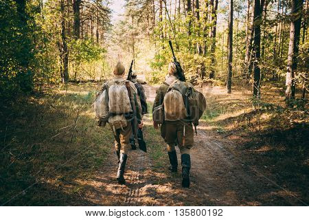 Two Unidentified Re-Enactors dressed As World War II Russian Soviet Soldiers In Camouflage Walks Through Forest On Road