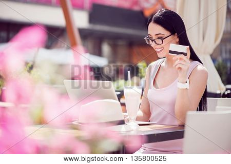Pay online. Cheerful content beautiful woman sitting at the table and holding credit card while using laptop