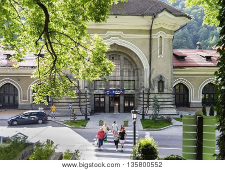 Sinaia, ROMANIA - June 18 2016: People crossing the street near Sinaia Royal Station, in Romania. SINAIA - June 18 2016