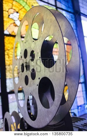 Reel of cinema projector. Old and antique part of commercial movie projector on a background of stained glass. Vintage projector. Mechanism of the aged theater projector.
