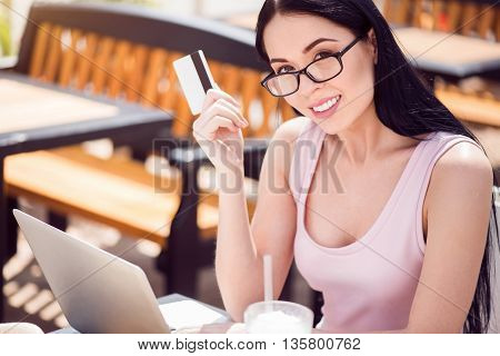 Positivity in mind. Cheerful beautiful smiling young woman holding credit card and sitting at the table while expressing gladness