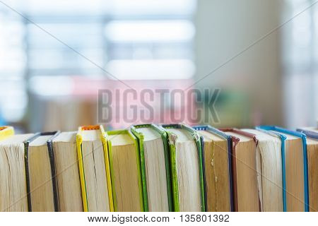 Close up of hard covered library books line up on a shelf selective focus with blurred background with text room for copyspace