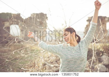 Natural woman enjoying sunny day outdoors dancing from happiness.Enjoyment.Enjoying nature with eyes closed,breathing fresh air.Stress free concept