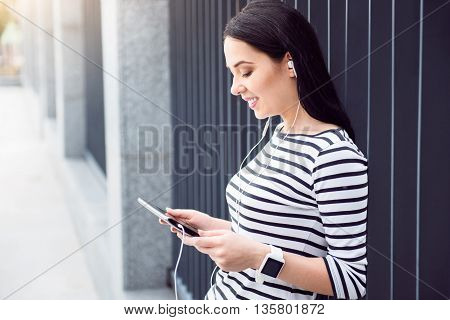 Urbanized by modern world. Pleasant delighted charming woman leaning on the fence and holding tablet while listening to music