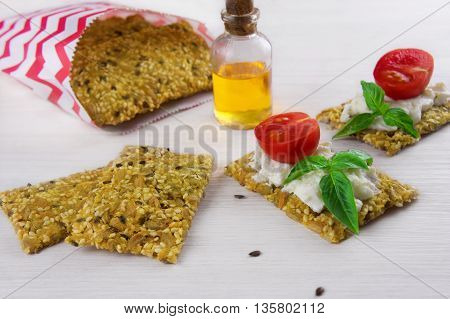 Homemade crisp bread with seeds and appetizers made of it with cream cheese and vegetables
