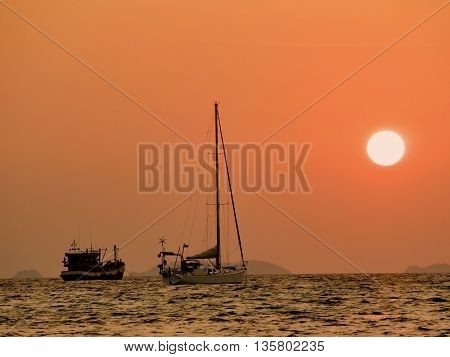 Defocus of Yachts in the sea at sunset. Silhouette boat at sunset over the sea with orange sky in background.