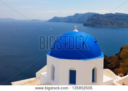view of volcano caldera and Aegan sea with blue church domes, Oia, Santorini