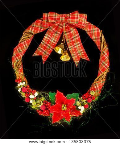 Christmas wreath isolated on black. Wreath with bells and puansetiey.