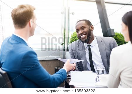 Here you are. Positive pleasant smiling colleagues talking and expressing positivity while sitting at the table