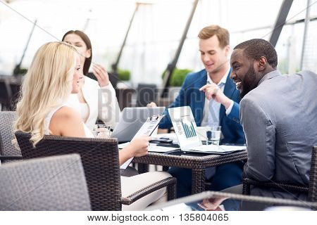 Vivid discussion. Pleasant cheerful colleagues sitting at the table and having a discussing while working on the project